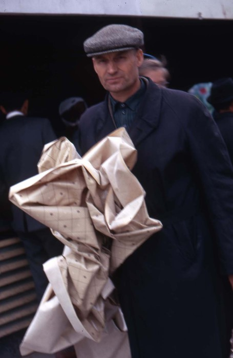Мужчина только что купивший за 25 копеек кусок клеенки. СССР, Новосибирск, 1969 год.