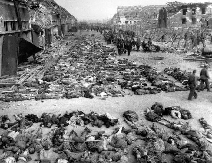 Американские солдаты ходят между рядами трупов, которые лежат на земле возле бараков в нацистском концентрационном лагере в Нордхаузене.