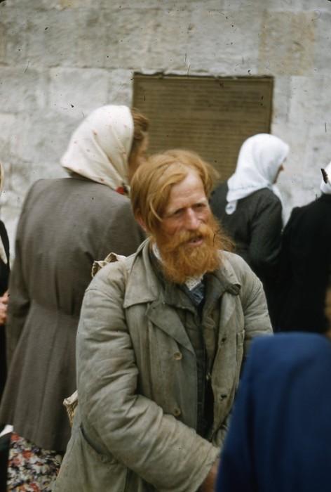 Приверженец старообрядческой веры возле православной святыни.