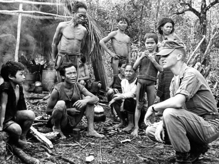 Американский военный инструктор позирует с группой местных жителей в окрестностях учебно-тренировочного лагеря в Центральном Вьетнаме, 17 ноября 1962 года.