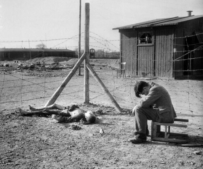 Молодой человек сидит на перевернутом табурете рядом с сожженным телом в лагере Фекла.