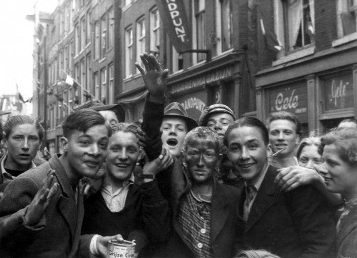 Молодые голландцы позируют с девушкой, поддерживавшей связи с немцами. Амстердам, май 1945 года. У девушки отрезаны волосы, лицо вымазано дегтем.