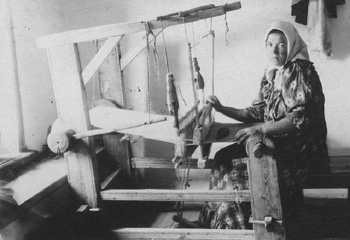 Работница, занимающаяся изготовлением ткани на ткацком станке.