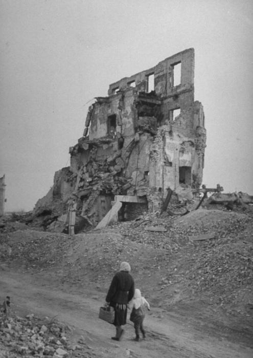Женщина с ребенком идущая среди развалин.