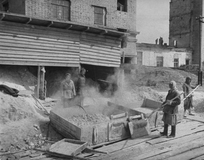 Женщины смешивающие известь и раствор для реконструкции разрушенных зданий в Сталинграде.
