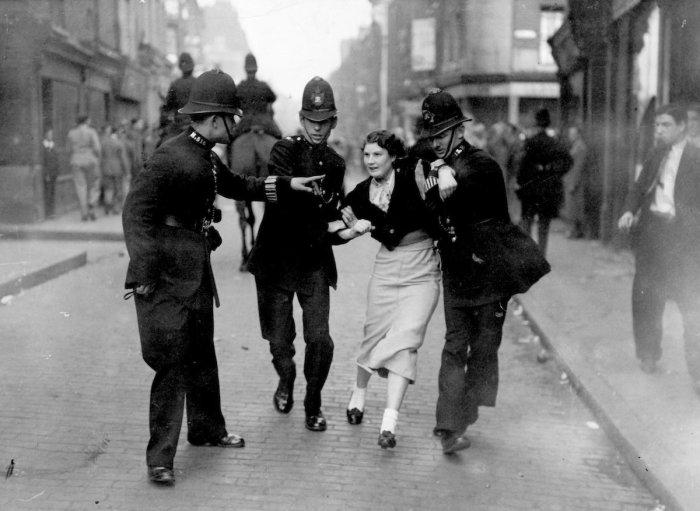 Полицейские арестовывают демонстрантку во время столкновения между коммунистами и британскими фашистами.