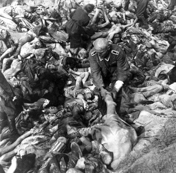 Немецкий солдат СС среди сотен трупов во время массового захоронении в Бельзене.