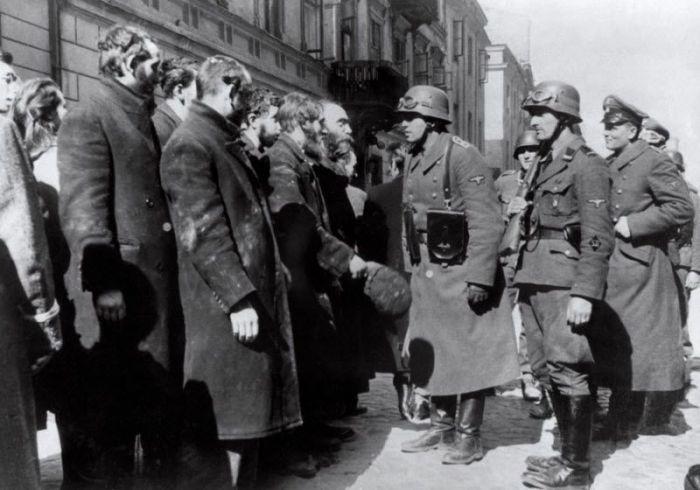 Немецкие солдаты проводят допрос евреев после восстания, состоявшегося в Варшавском гетто в 1943 году.
