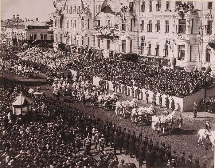 Коронационная карета императрицы Александры Федоровны проезжает мимо трибун со зрителями от Триумфальных ворот по Тверской улице.