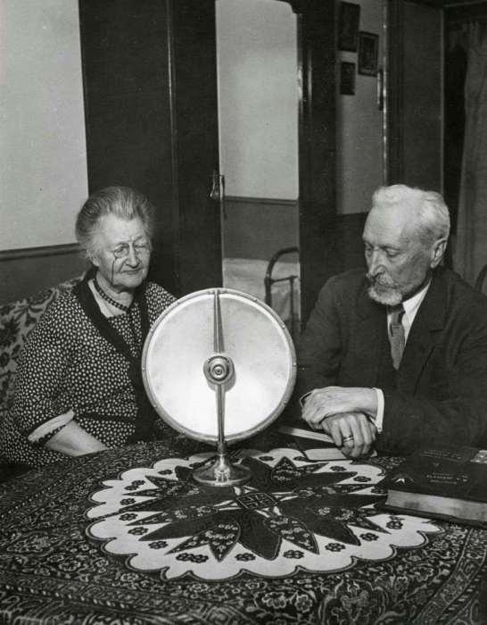 Русские аристократы, сидящие за столом и слушающие радио, проживающие в небольшом доме в пригороде Парижа. Франция, 1931 год.