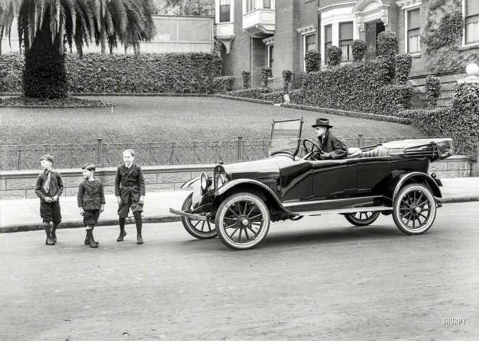 Дети переходят улицу перед остановившимся автомобилем в 1920 году.