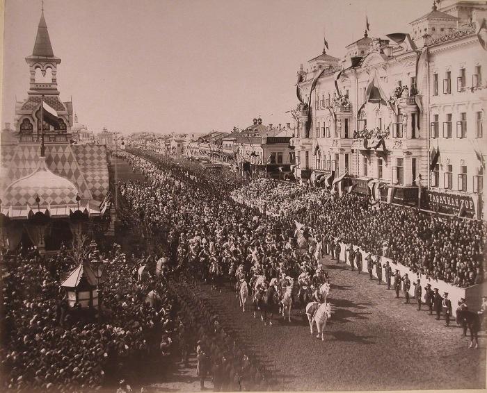 Император Николай II в сопровождении свиты шествует перед трибунами от Триумфальных ворот по Тверской улице.