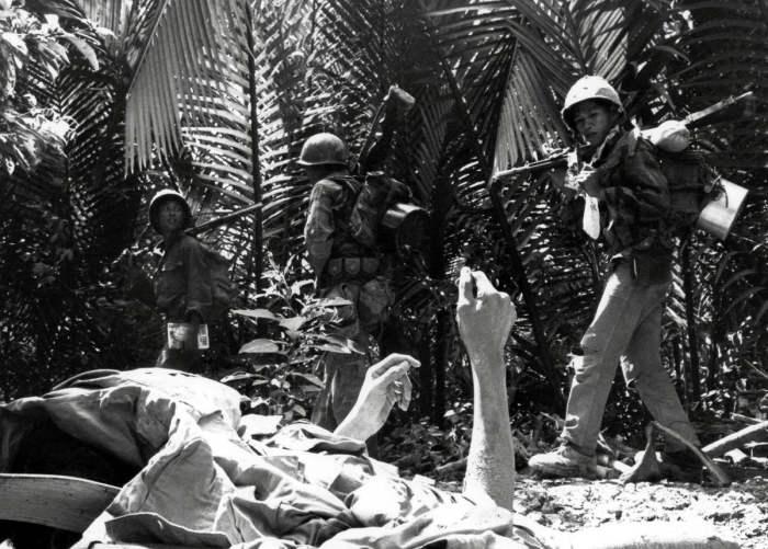 Смертельно раненый партизан Северного Вьетнама на фоне проходящих мимо южновьетнамских морских пехотинцев, осуществляющих поиск сил повстанцев в дельте Меконга, 27 февраля 1964 года.