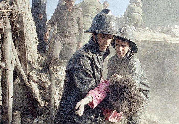 Афганские пожарные и девочка, погибшая в результате мощного взрыва в центре Кабула, 14 мая 1988.