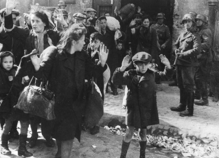 Группу евреев, в том числе маленького мальчика, выводят из Варшавского гетто в сопровождении немецких солдат.