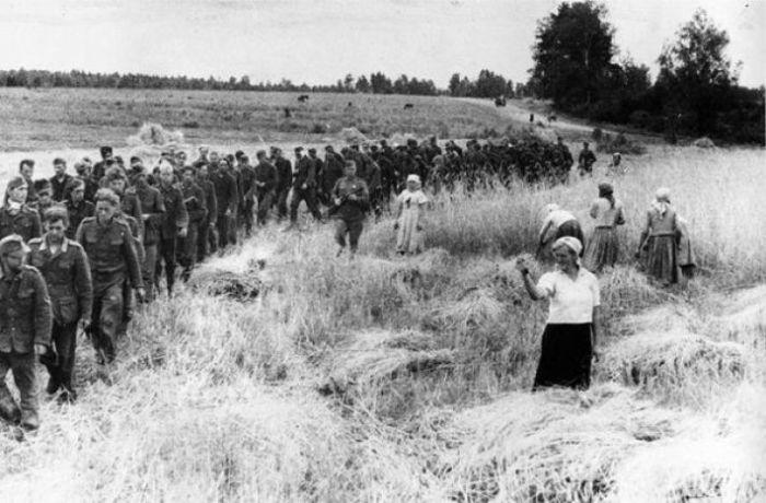 Женщина грозит кулаком пленным нацистам. СССР, 1944 год.