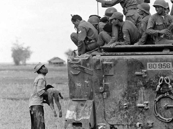 Отец держит тело своего убитого ребенка перед южновьетнамскими рейнджерами, смотрящими на него с бронетранспортера, 19 марта 1964 года.