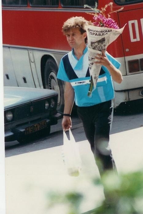 Мужчина несет цветы любимой женщине. СССР, Москва, 1984 год.
