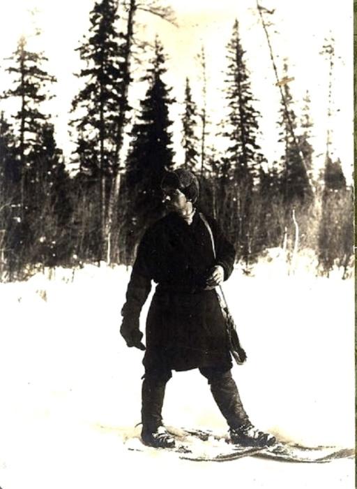 Охотник стоит на широких коротких лыжах, крепящихся к ступне ремешками.