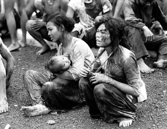 Мирные люди, которые вышли из своих подземных укрытий после двухдневной бомбардировки и тяжелых боёв в окрестностях города Донг Хой. Вьетнам, 6 июня 1965 года.