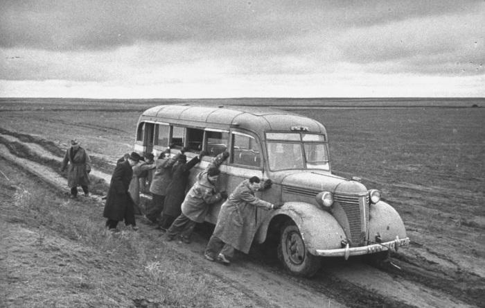 Иностранные корреспонденты, помогающие толкать автобус, который увяз в грязи за пределами города, когда они пересекали место прошлых боев.