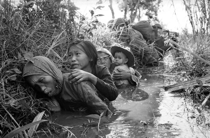 Вьетнамские женщины и дети прячутся от артиллерийского огня в заросшем канале в 30 км к западу от Сайгона, 1 января 1966 года.