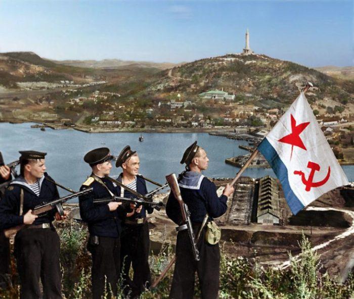 Советские моряки поднимают флаг ВМФ СССР над бухтой Порт-Артура в 1945 году.