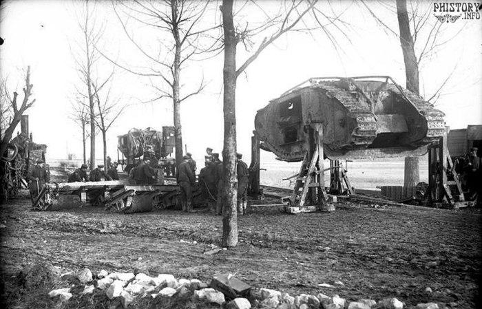Немецкие солдаты грузят на железнодорожную платформу захваченный британский танк Mark I.