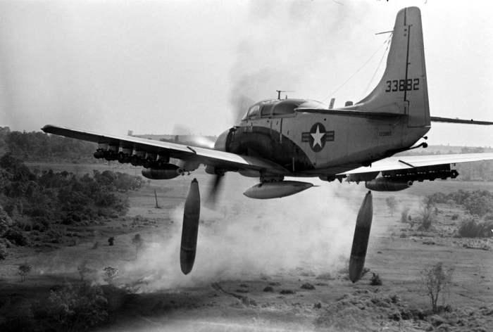 Американский штурмовик Douglas A-1 Skyraider сбрасывает бомбы напалмовые бомбы на позиции войск Северного Вьетнама, 26 декабря 1964 года.
