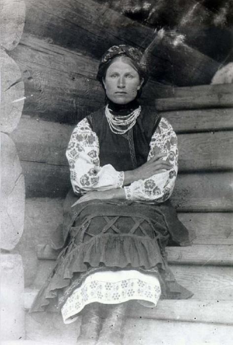 Женщина в традиционном украинском костюме, сидящая на ступеньке крыльца.