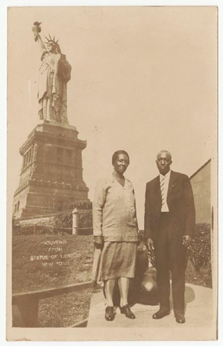 Афроамериканская пара в повседневной одежде на фоне Статуи Свободы.