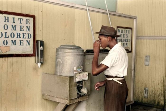 Афроамериканец пьет из автомата для питьевой воды.