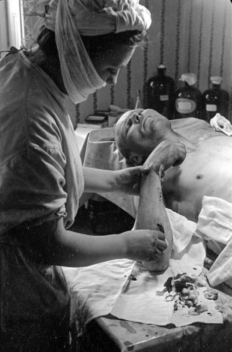 Медик обрабатывает рану на руке советского бойца в госпитале.