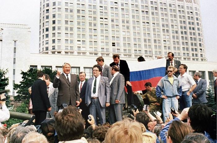 Президент России Борис Ельцин стоит на бронированном автомобиле на стоянке перед Белым домом. 19 августа 1991.