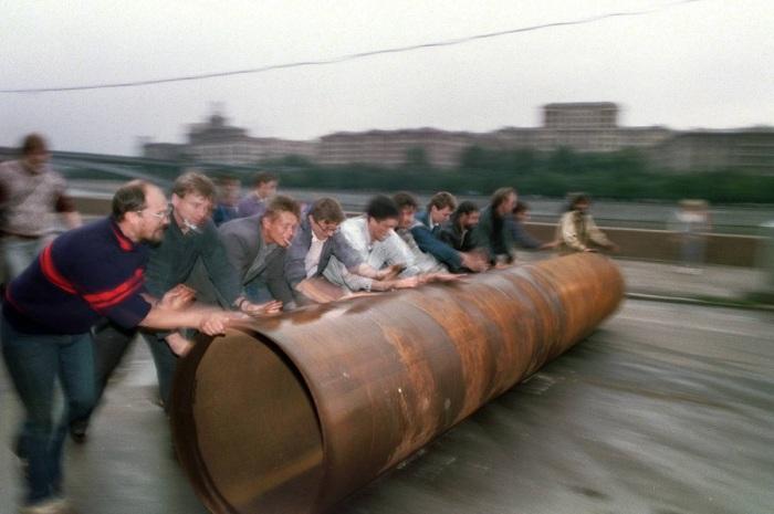 Сторонники президента России Бориса Ельцина катят большую металлическую трубу, чтобы использовать ее на баррикадах у Белого дома. 19 августа 1991.