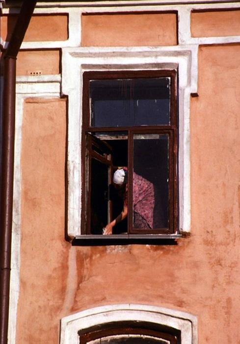 Женщина, моющая рано утром окно. СССР, Иркутск, 1988 год.