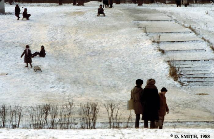 Дети, катающиеся на санках по склону холма. СССР, Москва, 1988 год.