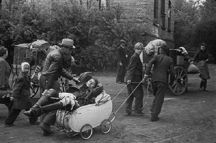 Мирные жители везут раненую женщину в детской коляске в пригороде Берлина.