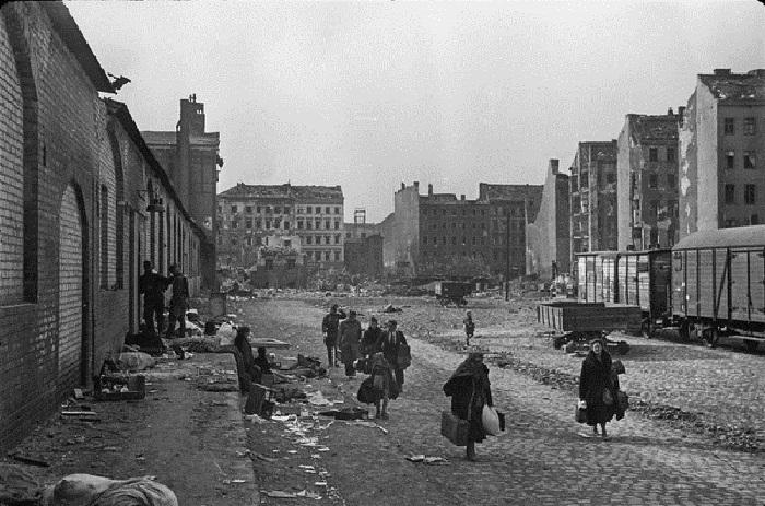 Мирные жители с вещами идут по улице разрушенного Берлина.