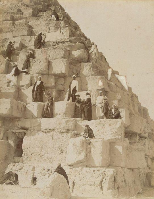 Европейские туристы и местные гиды поднимаются на одну из пирамид в Гизе.