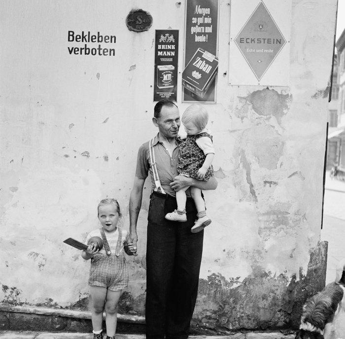 Отец с двумя детьми возле стенки, на которой вопреки запрету висят рекламные плакаты. Германия, 1955 год.