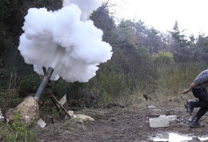 Боевики Свободной Сирийской армии, стреляющие из миномётов. Северо-запад Сирии, провинция Латакия, район Джебель-аль-Akrad. 25 февраля 2014 года.