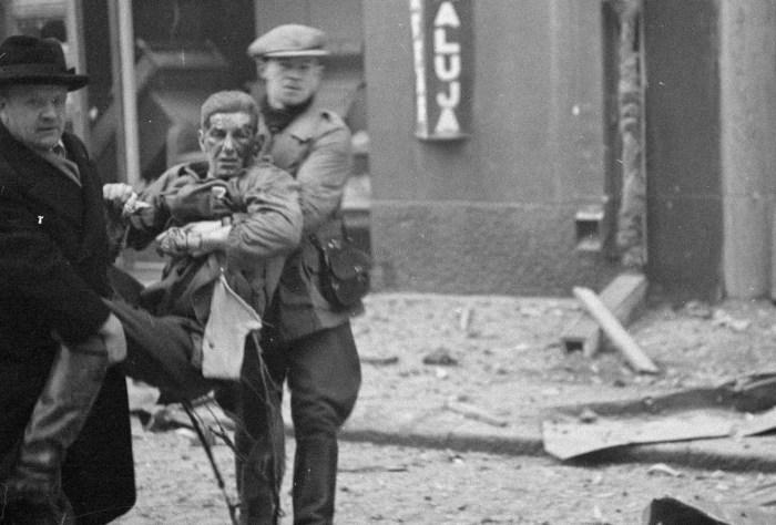 Раненый, которого эвакуируют из здания, поврежденного в результате воздушных бомбардировок.