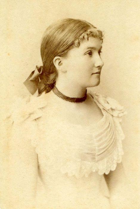 Девушка в платье с коротким ожерельем на шее.