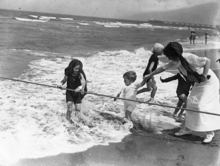 В начале XX века не было надувных матрасов, нарукавников и плавательных кругов. Поэтому дети купались с помощью специальных канатов, обеспечивающих некую безопасность. Пляж в Трувиль, Франция, 1913 год.