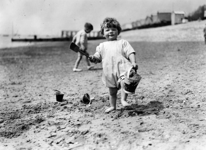 Ведёрко и лопатка - неизменные атрибуты детских игр на пляже вот уже почти 100 лет. Ребёнок на пляже в Саутенд. Англия, 1922 год.