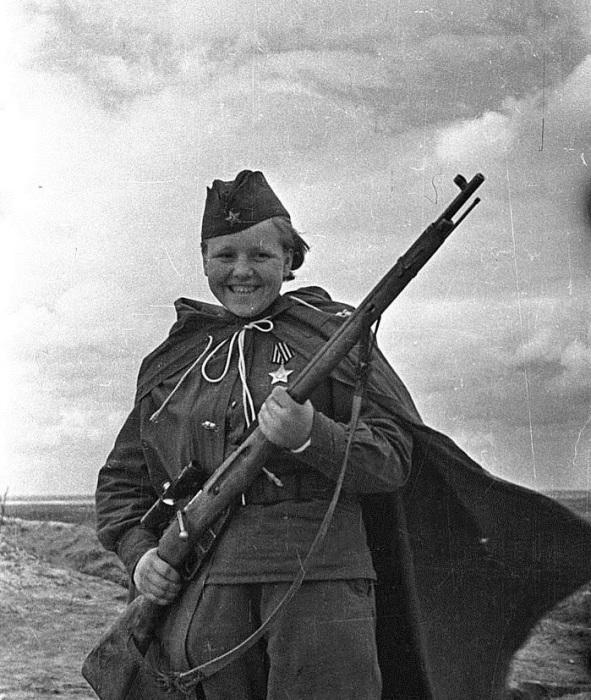 Кавалер ордена «Славы» 3 степени, снайпер Мария Кувшинова, уничтожившая 23 немецких солдата и офицера. На момент прибытия на фронт её было 16 лет (приписала 3 года). Мария Григорьевна прошла через освобождение Орши, Минска, взятие Кенигсберга и прорыв обороны противника в районе Мазурских озёр. После войны работала в Нижнем Тагиле на металлургическом комбинате и воспитывала двоих сыновей. Снимок сделан в мае 1944 года Михаилом Савиным.