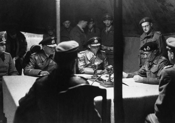 Британский фельдмаршал Бернард Монтгомери читает пакт о капитуляции в присутствии немецких офицеров.