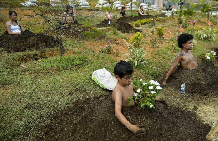 Местные жители принимающие участие в представлении которое включает в себя захоронение по пояс в рамках празднования Национальной недели памяти. Колумбия, Медельн.