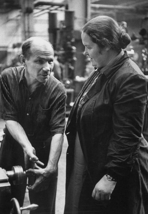Мужчина, объясняющий женщине принцип работы за станком. СССР, Москва, 1956 год.